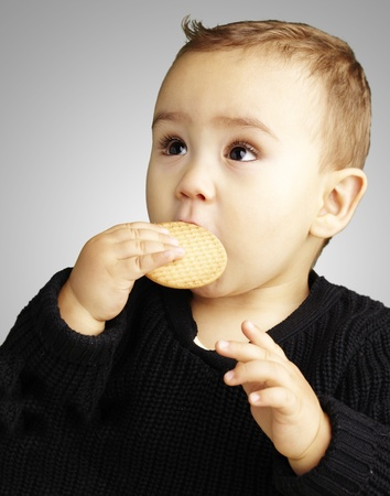 young boy eating a biscuit against a grey background photo