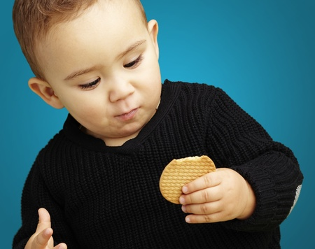young boy holding a biscuit against a blue background photo