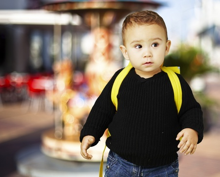 young boy carrying a yellow backpack against a carousel background photo