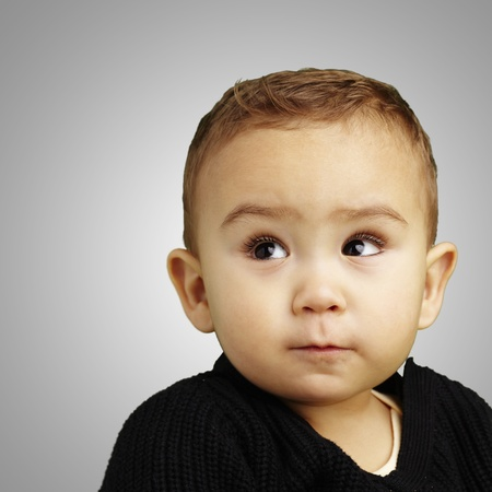handsome young boy looking up against a grey background Stock Photo - 13486256