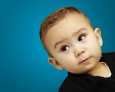 handsome young boy looking up against a blue background Stock Photo - 13486254