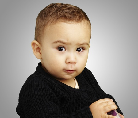 bored face: handsome young boy posing against a grey background