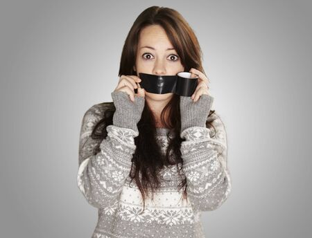 young girl covering her mouth with a black tape against a grey background photo