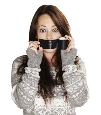 young girl covering her mouth with a black tape against a white background photo