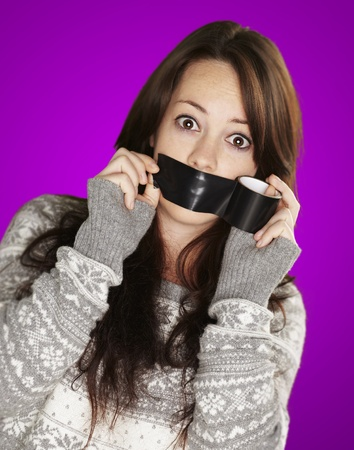 young girl covering her mouth with a black tape against a purple background photo