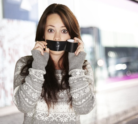 young girl covering her mouth with a black tape, outdoor photo