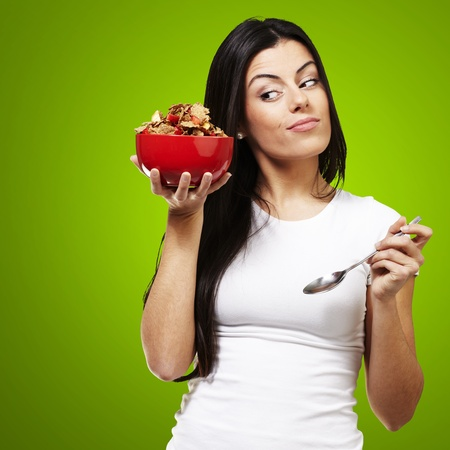 woman holding a delicious red breaksfast bowl against a green background photo