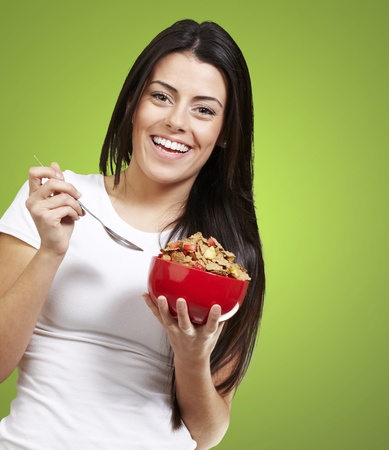 cornflakes: woman holding a delicious red breaksfast bowl against a green removable chroma background background background