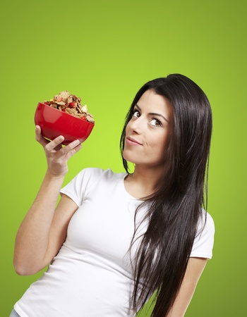 woman holding a delicious red breaksfast bowl against a green background Stock Photo - 12778949