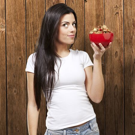 woman holding a delicious red breaksfast bowl against a wooden background photo