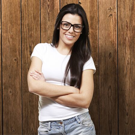 pretty young woman with glasses crossing her arms against a wooden background Stock Photo - 12778960