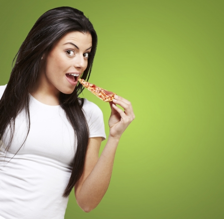 young woman eating a piece of pizza against a green background Stock Photo - 12778935