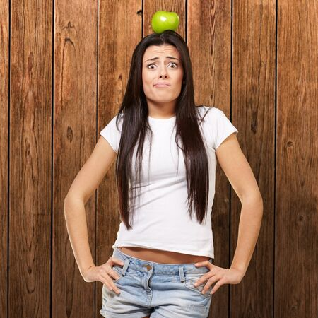 portrait of young woman holding green apple on her head against a wooden wall photo