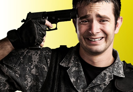 portrait of young soldier suiciding against a yellow background photo