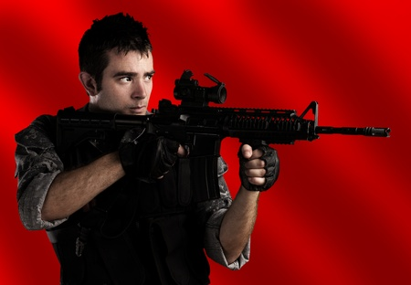 portrait of young soldier aiming with rifle against a red background photo