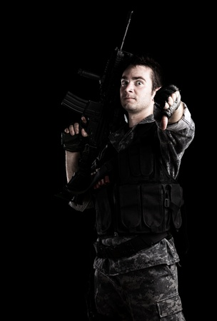 iraq war: young armed soldier with finger down on a black background Stock Photo