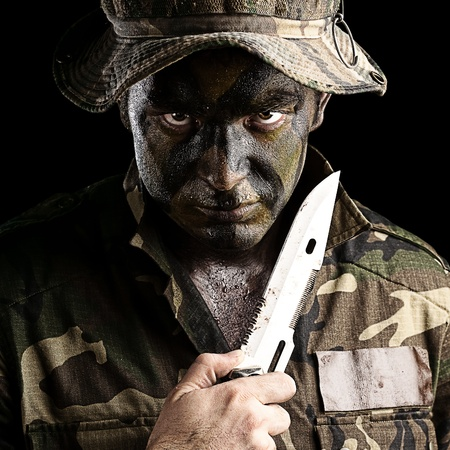 young knife: portrait of young soldier with knife and hat against yellow background Stock Photo