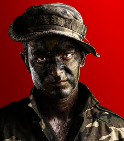young soldier face with jungle camouflage on red background Stock Photo - 13156595