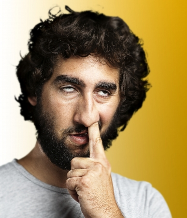 bored face: young man sticking his finger in his nose against a yellow background