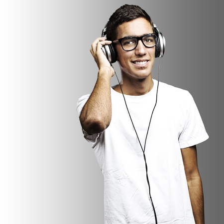 portrait of young man with glasses and headphones listening to music on a grey background photo
