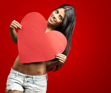 portrait of young woman holding red heart against a red background photo