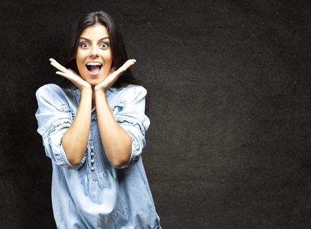 portrait of surprised young woman against a grunge wall photo