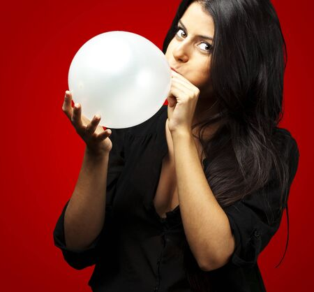 portrait of young woman blowing balloon against a red background photo