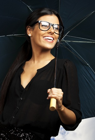 young pretty woman with umbrella against a cloudy sky background photo