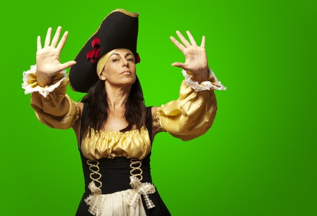 portrait of pirate woman gesturing stop against a green background photo