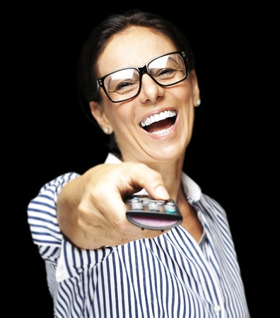 portrait of middle aged woman laughing using remote control tv against black background photo
