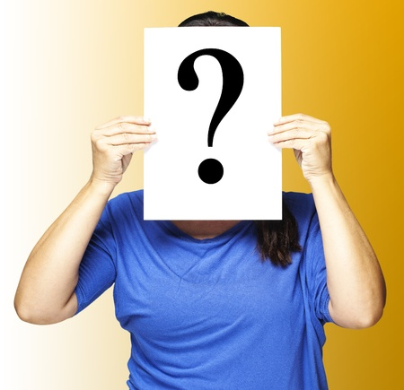suspicious: portrait of a middle aged woman holding a interrogation symbol over orange Stock Photo