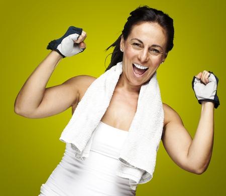 полотенце: Молодой спортивный женщина делает жест победителя на зеленом фоне