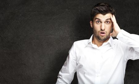 cara sorprendida: retrato de hombre joven sorprendió contra una pared del grunge Foto de archivo