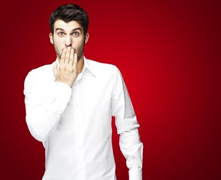 Portret van een jonge man die zijn mond met de hand over de rode
