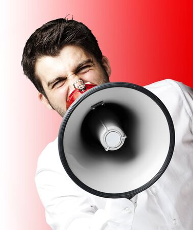 man screaming: portrait of young man shouting with megaphone over red background