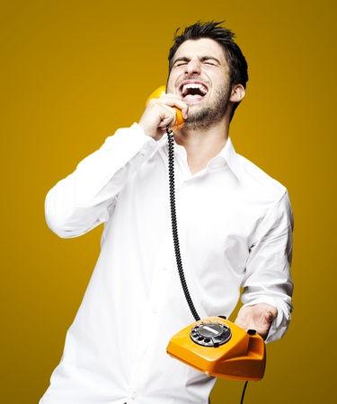 portrait of young man talking using vintage telephone laughing over orange background photo