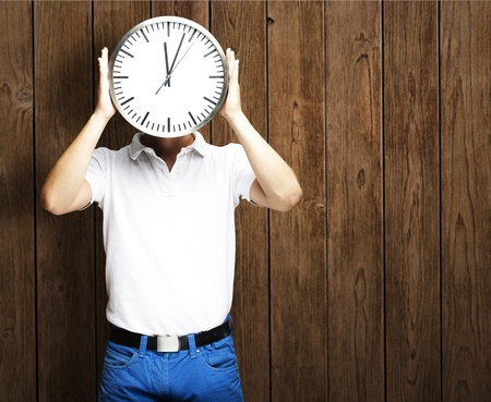 portrait of man holding clock against a wooden wall photo