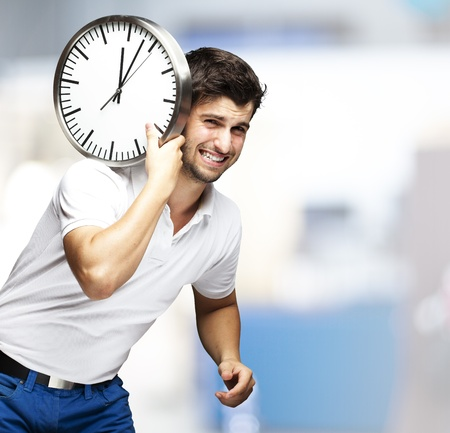 young man holding a clock on his back, indoor photo