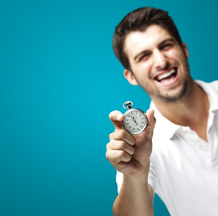 portrait of young man holding a stopwatch against a blue background photo