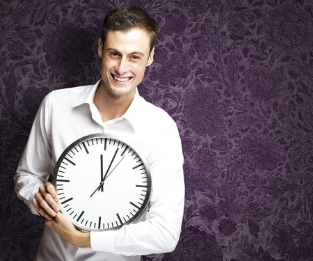 portrait of young man holding clock against a vintage background photo