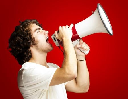 hangos: Portré egy jóképű fiatalember kiabál hangszóró ellen piros háttér Stock fotó