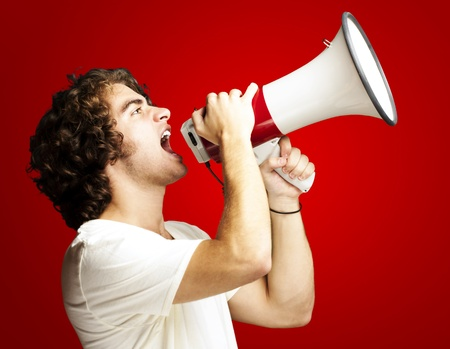 loud speaker: portrait of a handsome young man shouting with megaphone against a red background