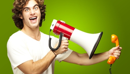 portrait of young man shouting with megaphone and talking on vintage telephone over green photo