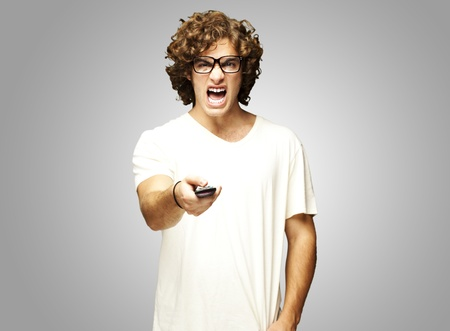 remote communication: portrait of a handsome young man changing channel against a grey background