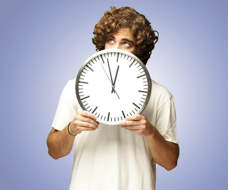 looking at watch: scared young man hidden behind a clock against a blue background