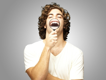 teeths: portrait of young man with magnifying glass showing his teeths over grey background Stock Photo