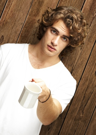 portrait of young man offering cup against a wooden wall