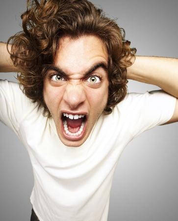 faccia disperata: Ritratto di giovane uomo furioso gridare contro uno sfondo grigio