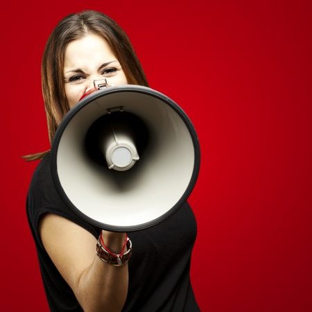 public speaker: portrait of young woman shouting with megaphone over red Stock Photo
