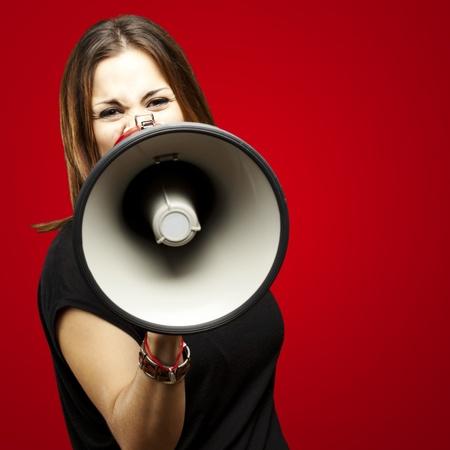 hablar en publico: Retrato de mujer joven con megáfono gritando sobre rojo